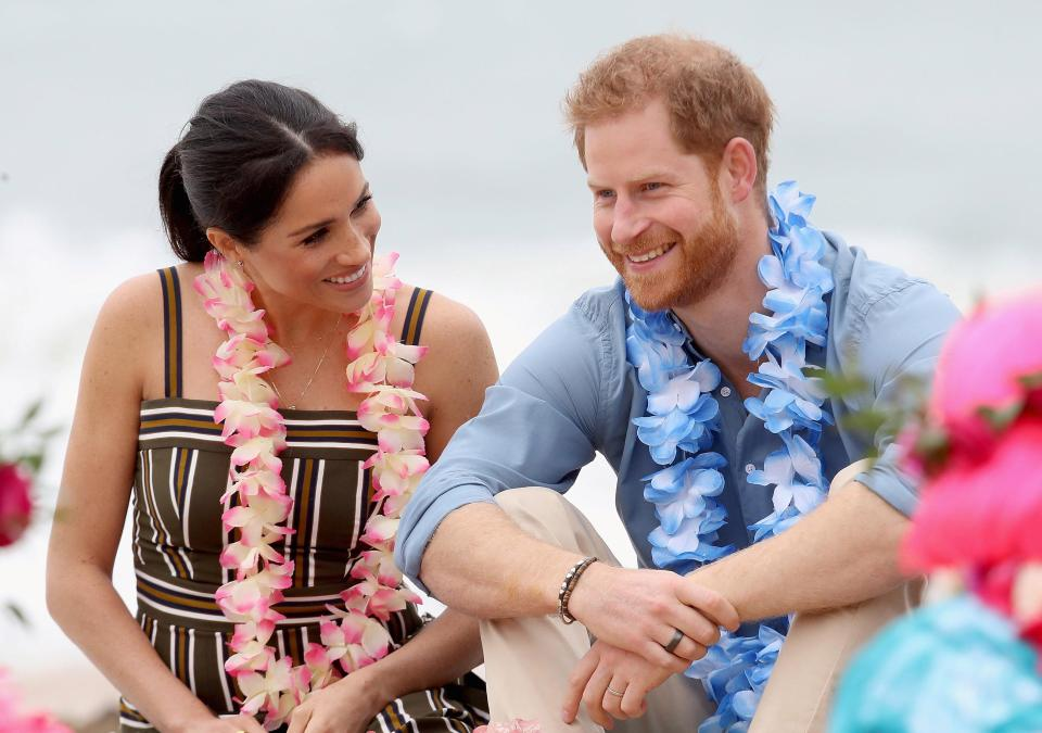 Meghan cradles her baby bump on Sydney beach and wears £880 maxi dress before she and Harry kick off their shoes to join an 'anti-bad vibes circle' with surfing mental health group