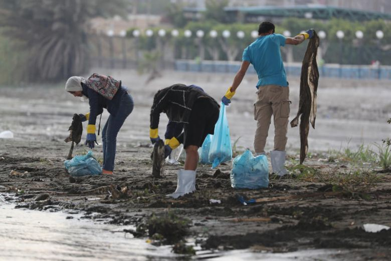 A volunteer collects waste and plastic as part of a campaign to clean up the Nile River, in Cairo