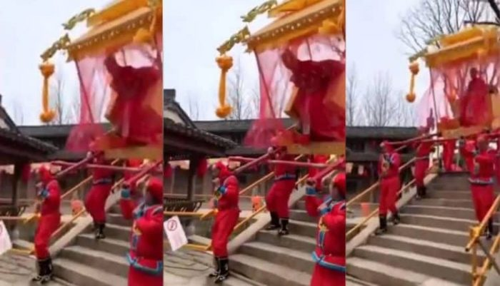 Woman tumbles out of sedan chair going downhill over bridge