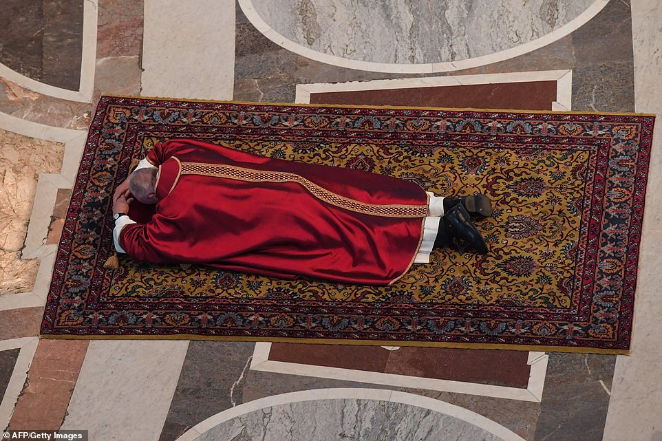 Pope Francis prostrates himself in St Peter's Basilica for Good Friday service as he rests his head on a red pillow and prays