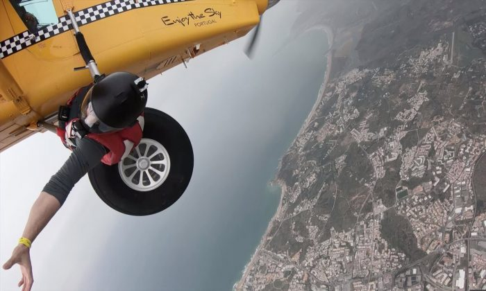 Bananas! Bizarre moment a daredevil climbs out of a plane to take fruit from a wingsuit flier